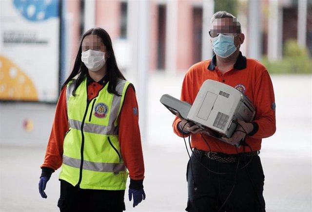 Dos trabajadores del SAMUR protección civil de Madrid protegidos con mascarilla acuden a IFEMA durante el tercer día de funcionamiento y primera fase del hospital provisional desplegado -por el momento- en los pabellones 5, 7 y 9 del recinto
