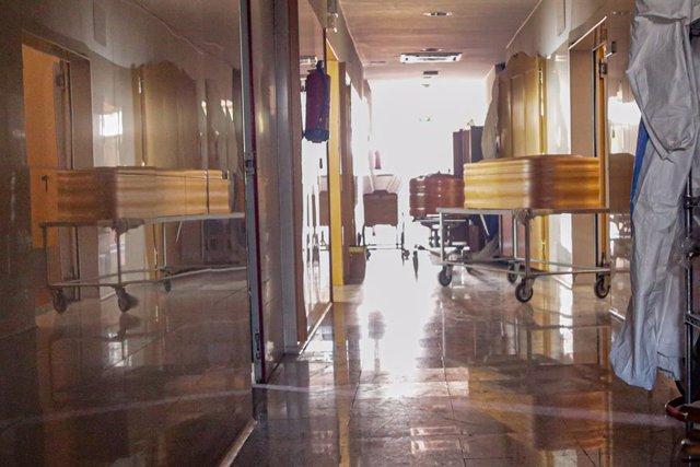Varios ataúdes y varios trajes de protección en un pasillo del Tanatorio Crematorio Mémora Coslada.