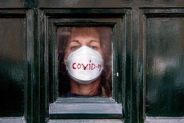 Mujer con mascarilla por el coronavirus en La Haya