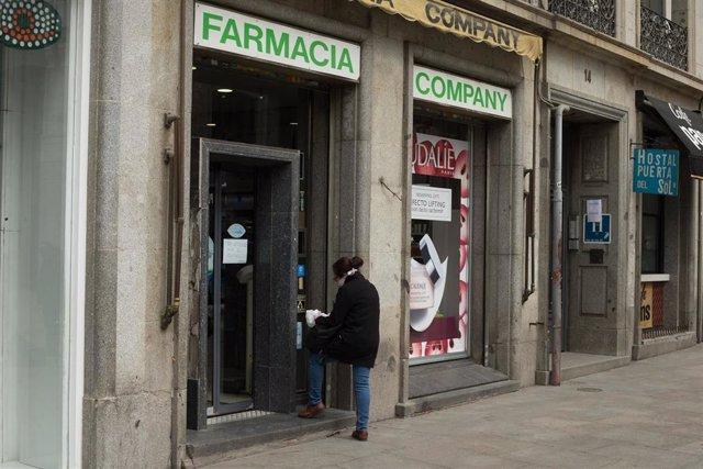 Una mujer entra en una farmacia del centro de la capital que amanece totalmente vacía durante el sexto día de confinamiento por coronavirus en el país, en Madrid, (España), a 20 de marzo de 2020.