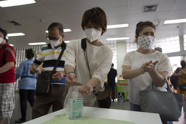 Un grupo de personas se desinfectan las manos con gel antes de entrar a un supermercado en Bangkok, Tailandia.