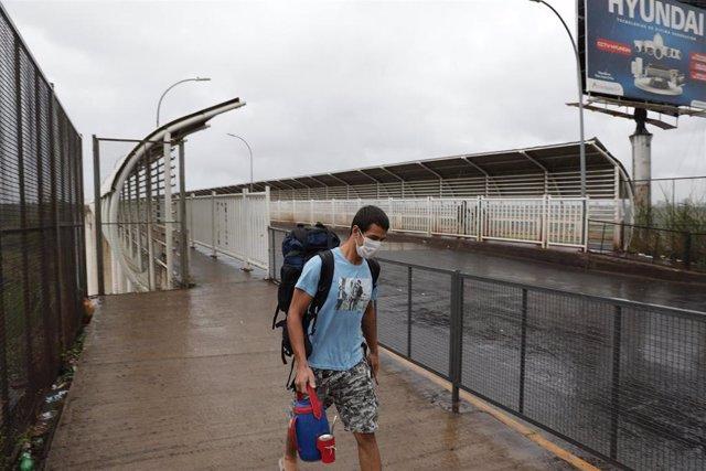 Un hombre con mascarilla por el coronavirus en el puente internacional que conecta Paraguay y Brasil
