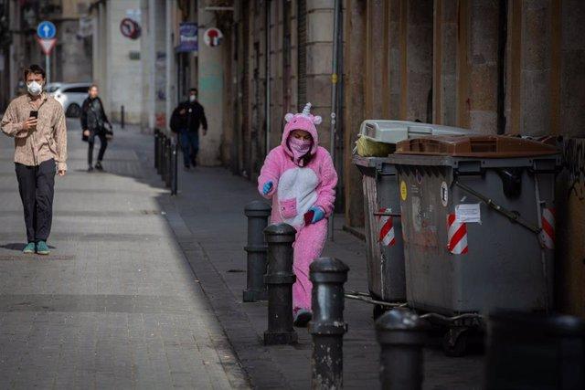 Una mujer con un traje de unicornio y protegida con mascarilla y guantes durante el primer día laborable de la segunda semana desde que se decretó el estado de alarma en España a consecuencia del coronavirus.