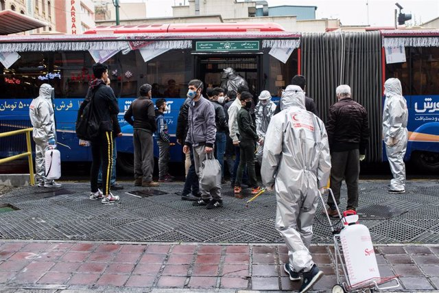 Trabajadores voluntarios desinfectando un autobús en Teherán