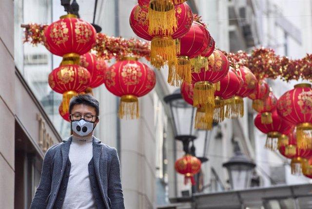 Un home amb màscara camina pels carrers de Hong Kong.