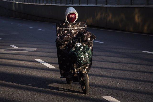 Una mujer en moto por las calles de la ciudad de Wuhan, epicentro de la epidemia del nuevo coronavirus