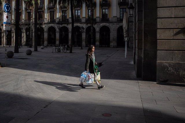 Una dona camina amb diverses borses després d'haver fet la compra, a Barcelona/Catalunya (Espanya) a 18 de març de 2020.