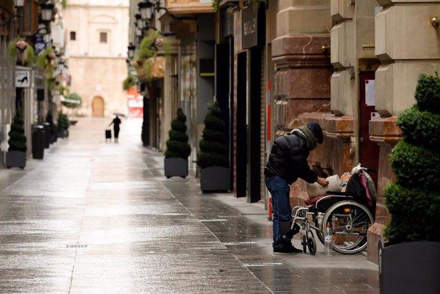 Una persona junto a una silla de ruedas en la calle Platería, vacía durante el estado de alarma, en Murcia (España) a 22 de marzo de 2020.