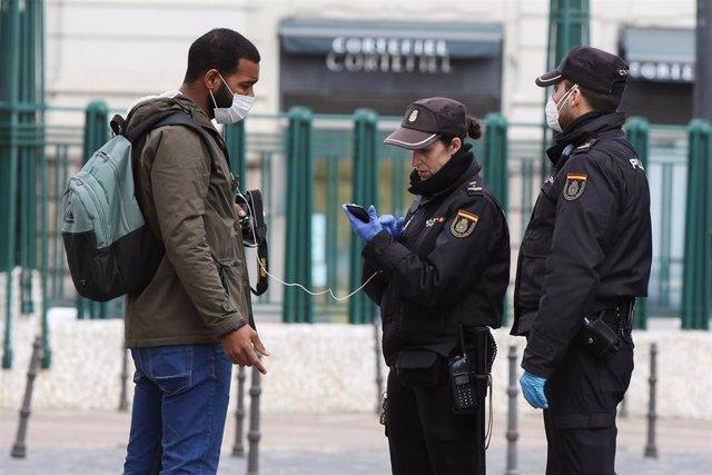 Agentes de Policía requieren la documentación a un ciudadano en uno de los controles por el covid-19