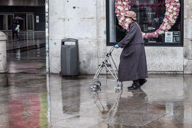 Una mujer protegida con mascarilla camina con un andador por la céntrica Puerta del Sol, prácticamente vacía durante el primer día laborable de la segunda semana desde que se decretó el estado de alarma en el país a consecuencia del coronavirus, en Madrid
