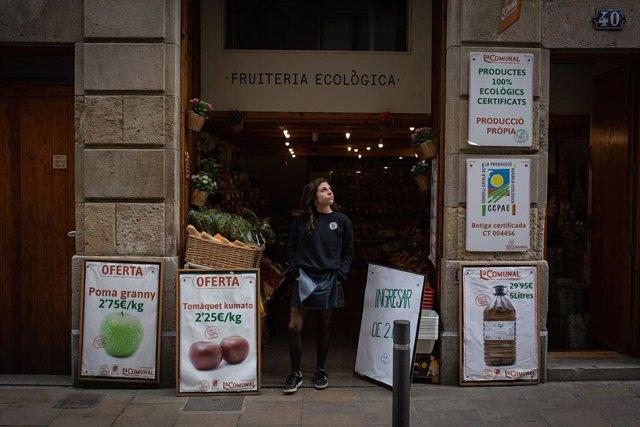 Una dona en la porta de la seva frutería ecològica durant el primer dia laborable de la segona setmana des que es va decretar l'estat d'alarma al país a conseqüència del coronavirus, a Barcelona/Catalunya (Espanya) a 23 de març de 2020.