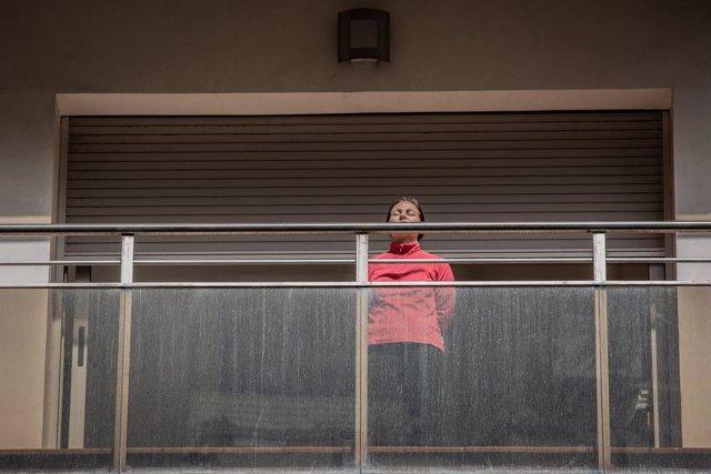Una dona pren el sol en la seva terrassa durant el primer dia laborable de la segona setmana des que es va decretar l'estat d'alarma al país a conseqüència del coronavirus, a Barcelona/Catalunya (Espanya) a 23 de març de 2020.