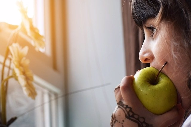 Comiendo una manzana mirando por la ventana melancólica.