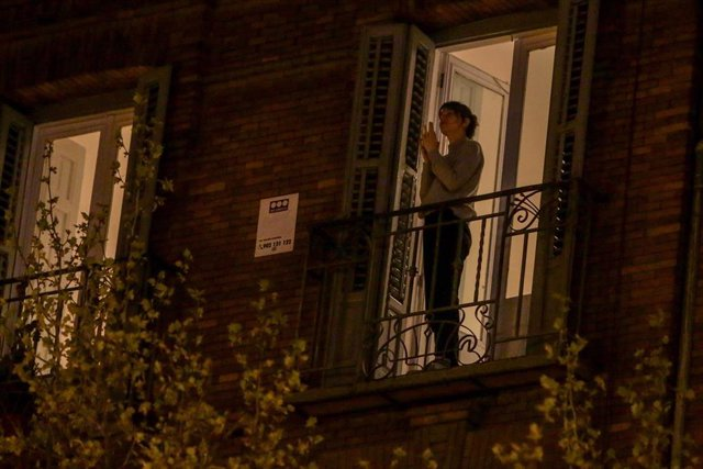 Una mujer aplaude desde su balcón por la labor que están realizando los sanitarios ante la crisis de contagios por el coronavirus, en Madrid (España), a 17 de marzo de 2020.