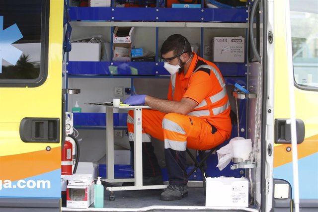 Dispositivo sanitario de la prueba test del PCR para detectar la infección por coronavirus a una persona desde su coche, instalado en el recinto de aparcamineto del centro de salud de la barriada La Roca, en Málaga, (Andalucía, España),