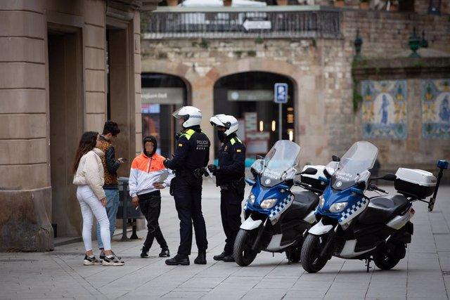 Dos agents de Policia parlen amb tres joves durant el segon dia laborable de l'estat d'alarma pel coronavirus, a Barcelona/Catalunya (Espanya), a 17 de març de 2020.