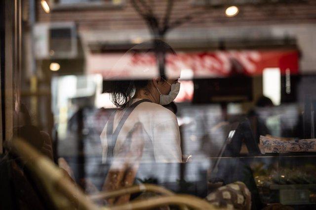 Una treballadora atén amb una mascarilla protectora durant el primer dia laborable de la segona setmana des que es va decretar l'estat d'alarma al país a conseqüència del coronavirus, a Barcelona/Catalunya (Espanya) a 23 de març de 2020.