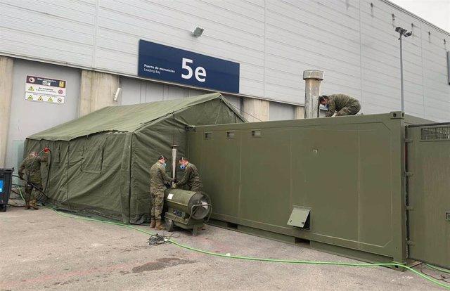 Militares del ejército acicalan la zona exterior perteneciente al pabellón 5 de IFEMA , durante el tercer día de funcionamiento y primera fase del hospital provisional desplegado -por el momento- en los pabellones 5, 7 y 9 de IFEMA.