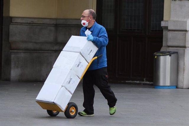 Un hombre con mascarilla y guantes carga con cajas.