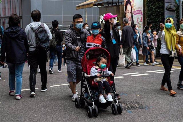 15 March 2020, China, Hong Kong: People with surgical face masks cross the street in Hong Kong, amid the Coronavirus outbreak. Photo: Keith Tsuji/ZUMA Wire/dpa