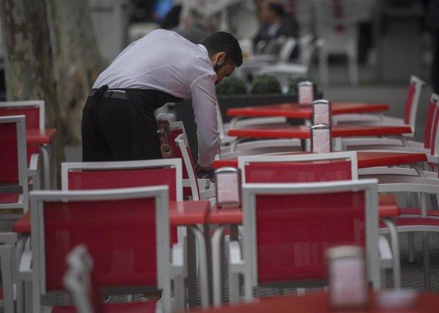 Un camarero limpia las mesas de un bar.
