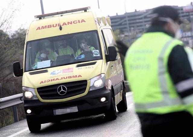 Sanitarios del SUMMA 112 de la Comunidad de Madrid totalmente protegidos conducen una ambulancia que se dirige a la entrada del recinto de IFEMA.
