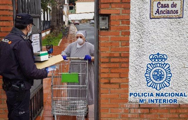 Un agente de Policía Nacional reparte mascarillas en un centro de ancianos en Málaga y Ronda frente al COVID-19