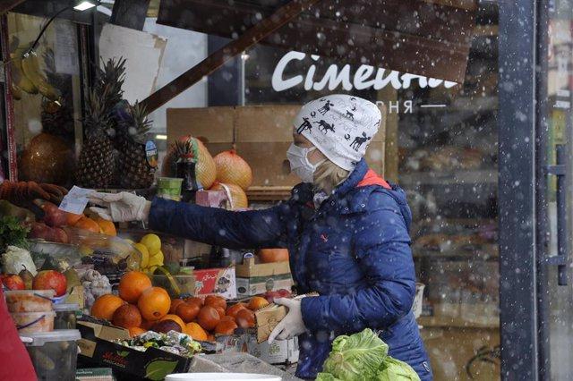 Una mujer con mascarilla en un mercado de Kiev