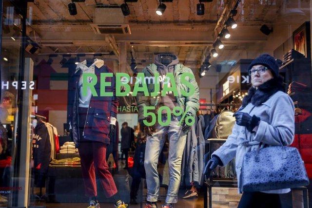 Una mujer pasea junto a una tienda de ropa en Madrid