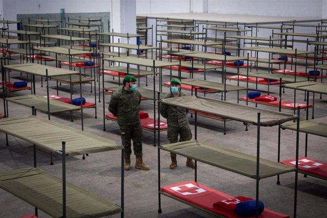 Militares protegidos con mascarilla en el pabellón de la Fira de Barcelona habilitado para acoger a personas sin hogar