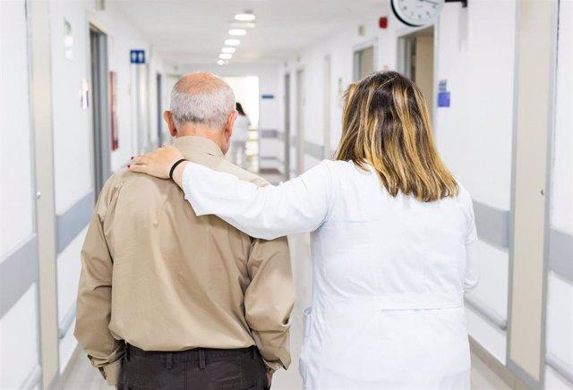 Un profesional sanitario acompaña a una persona mayor en un hospital
