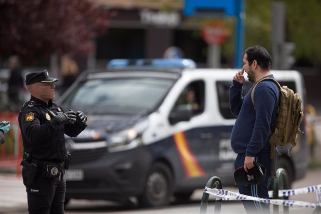 Un Policía Nacional habla con un transeúnte que caminaba por las inmediaciones del Palacio de Hielo de Madrid