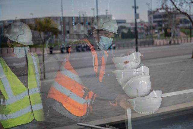 Dos trabajadores asiáticos colocan cascos blancos de obra en el pabellón del Mobile World Congress (MWC) durante el desmantelamiento de los stands de la feria, en Barcelona/Catalunya (España) a 13 de febrero de 2020.