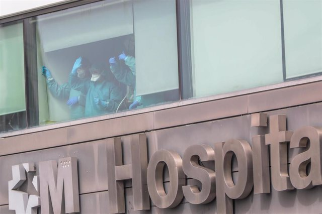 Sanitarios del Hospital de La Paz totalmente protegidos saludan desde una de las ventanas del centro
