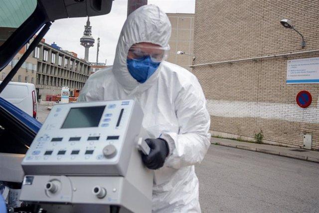 Un técnico protegido con un traje, guantes y mascarilla en el Hospital Gregorio Marañón, saca un respirador del maletero de su coche