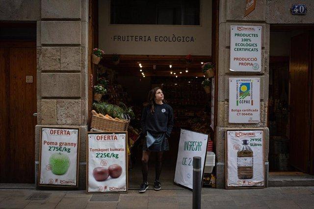 Una mujer en la puerta de su frutería ecológica durante el primer día laborable de la segunda semana desde que se decretó el estado de alarma en el país a consecuencia del coronavirus, en Barcelona/Catalunya (España) a 23 de marzo de 2020.