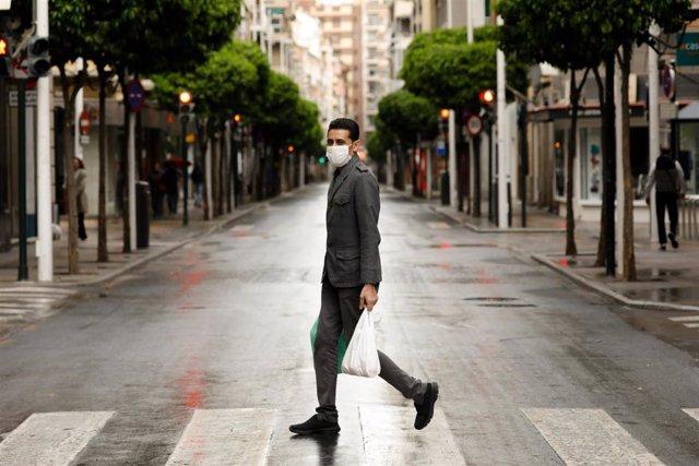 Una persona con mascarilla recorre la calle Alejandro Séiquer, vacía durante el estado de alarma, con bolsas de plástico en las manos, en Murcia (España) a 22 de marzo de 2020.