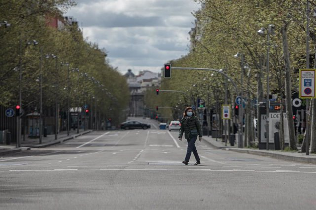 Una mujer pasea con mascarilla por el cruce entre la calle Serrano y la calle Ortega y Gasset, vacío durante el estado de alarma, a 22 de marzo de 2020.