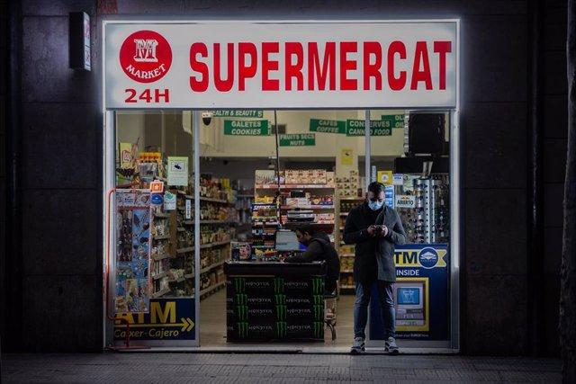 Un hombre protegido con una mascarilla en la puerta de un supermercado 24 horas abierto durante el primer día laborable de la segunda semana desde que se decretó el estado de alarma en el país a consecuencia del coronavirus, en Barcelona/Catalunya (España