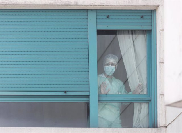 Una trabajadora del personal sanitario protegida con mascarilla se asoma por una de las ventanas de la Residencia ORPEA Madrid