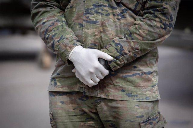 Manos de uno de los militares del ejército protegido con guantes que custodia el pabellón de la Fira de Barcelona que ya está habilitado para acoger a personas sin hogar en plena crisis del coronavirus, en Barcelona