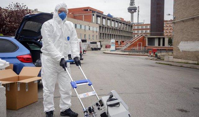 Un técnico protegido con un traje, guantes y mascarilla en el Hospital Gregorio Marañón antes de montar un respirador