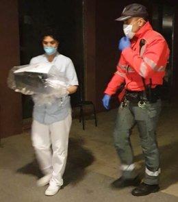 Un agente de Policía Foral entrega material donado por ciudadanos a personal sanitario para luchar contra el coronavirus.