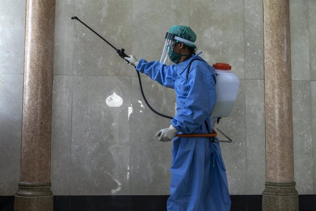 26 March 2020, Indonesia, Lhokseumawe: An Indonesian Military health officers wearing a protective suit sprays disinfectant at a Mosque as a preventive measure against the spread of coronavirus (COVID-19). Photo: Zikri Maulana/ZUMA Wire/dpa
