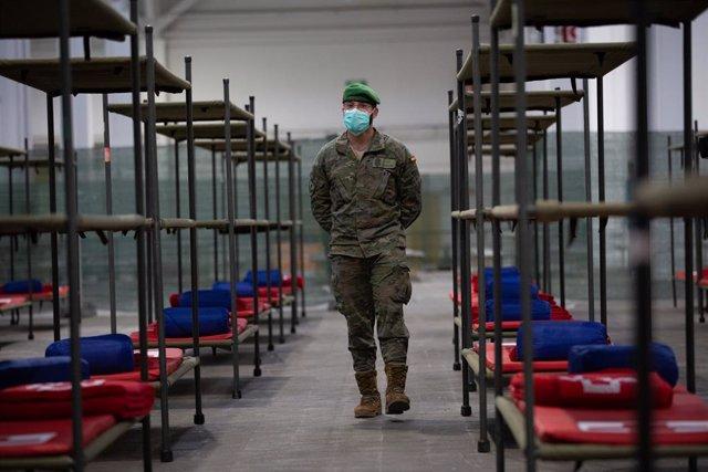 Un militar protegit amb màscara custodia el pavelló de Fira de Barcelona que ja està habilitat per acollir persones sense llar en plena crisi del coronavirus, Barcelona, Catalunya (Espanya), 25 de març del 2020.