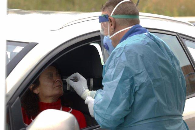Dispositivo sanitario de la prueba test del PCR para detectar la infección por coronavirus a las personas desde su coche, instalado en el recinto de aparcamiento del centro de salud de la barriada La Roca, en Málaga