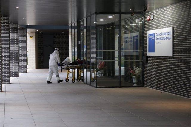 Un sanitario protegido con un traje, guantes y mascarilla, sale con una camilla en la que lleva a una persona a una residencia, en aislamiento, en Vitoria/Euskadi (España) a 18 de marzo de 2020.