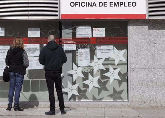 Dos personas leen los carteles de una oficina de empleo cerrada