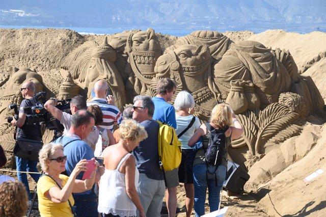 Un grupo de turistas visitan el Belén de Arena de la playa de Las Canteras tras su inauguración