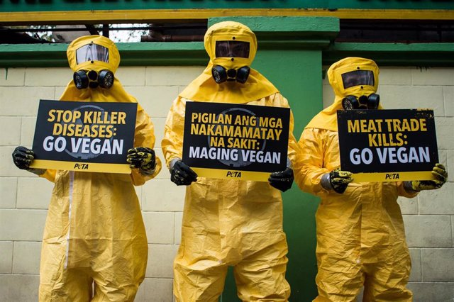 13 February 2020, Philippines, Manila: Supporters of the People for the Ethical Treatment of Animals (PETA) wear biohazard suits as they protest to demand everyone to go vegan and blame the consumption of meat for the spread of coronavirus, outside the Fi